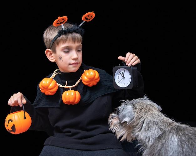 Halloween-lebensstil. ein junge mit einer spinne auf der wange und kürbisperlen, der einen orangefarbenen halloween-korb mit pralinen und einem schwarzen wecker hält, und ein hund, der den jungen auf schwarzem hintergrund ansieht