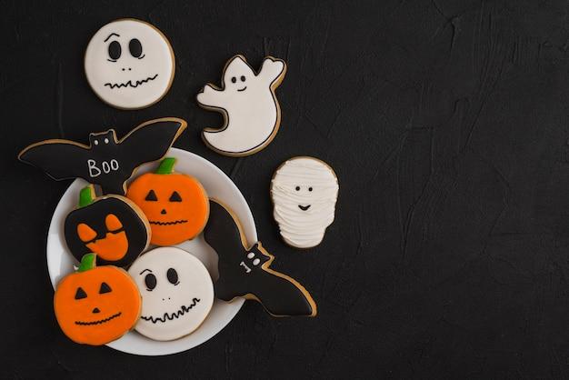 Halloween-lebkuchen auf platte nahe köstlichen plätzchen