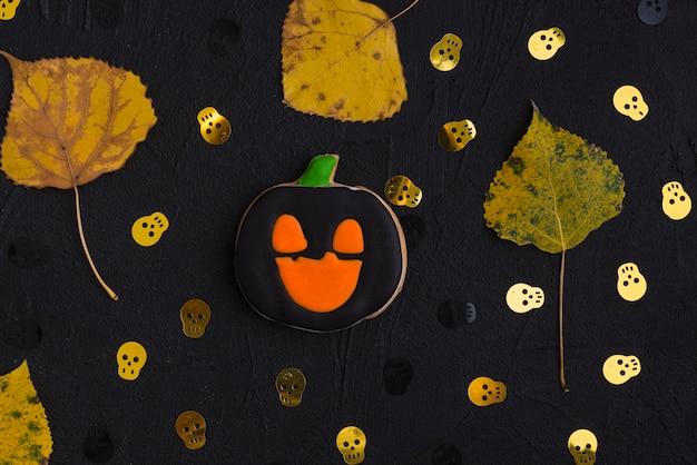 Halloween-lebkuchen, trockene blätter und dekorierende schädel