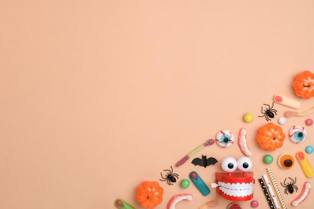 Halloween-leckereien auf einem orangefarbenen hintergrund. verschiedene süßigkeiten mit einem platz für text.