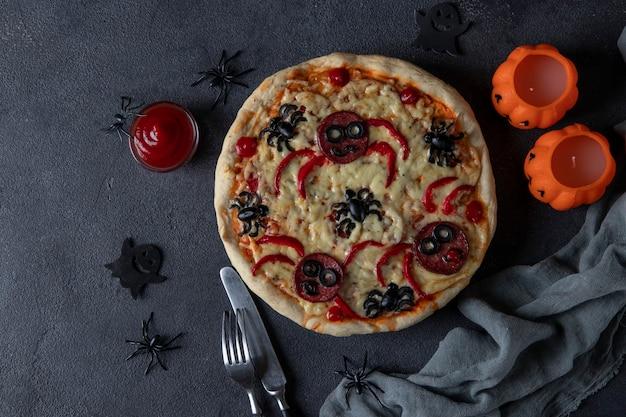Halloween lustige pizza mit spinnen, kreative idee für halloween pizza auf dunkelgrauem hintergrund, ansicht von oben