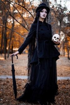 Halloween-mädchen, das einen schädel über dunklem furchtsamem hält