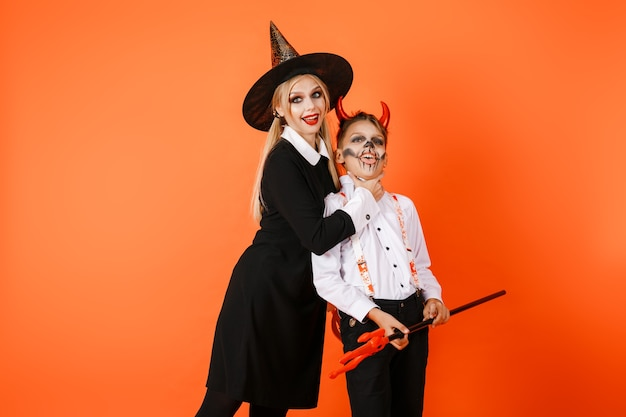 Halloween-mädchen in einem gruseligen kostüm, das von der kehle halloween-junge auf dem hintergrund einer orange wand gefangen wird. hochwertiges foto