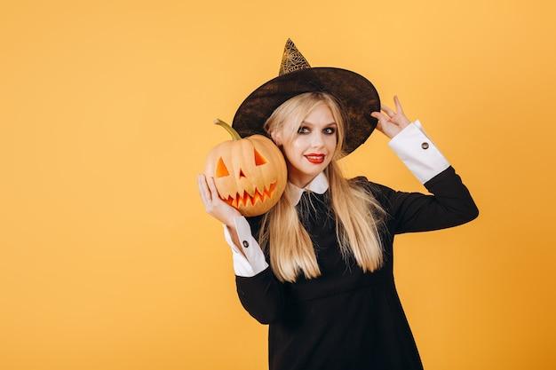 Halloween-mädchen in einem hexenkostüm mit einem kürbis in ihren händen auf einem orangefarbenen wandhintergrund. hochwertiges foto
