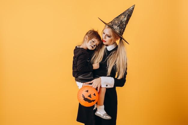 Halloween-mädchen in einem hut hält ein kleines mädchen mit einem gemalten schnurrbart einer katze auf einem hintergrund einer gelben wand, kopieren raum. hochwertiges foto