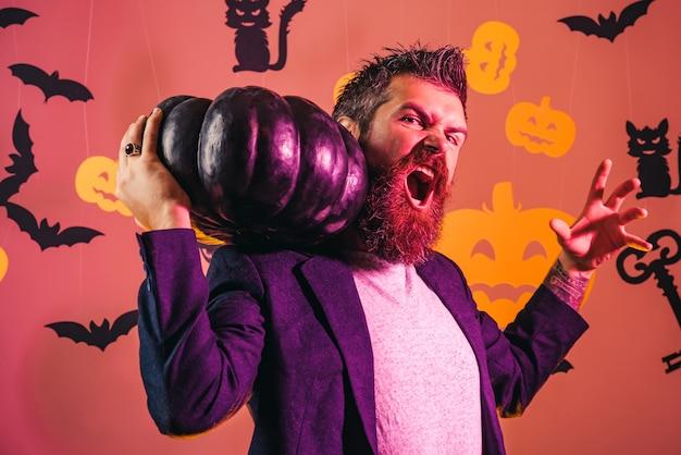 Halloween mann. hipster mit blutigem bart halten kürbis.