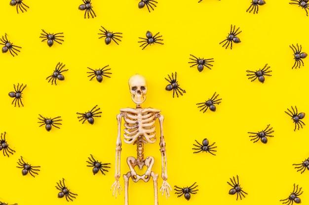 Halloween minimale dekorationskomposition mit vielen schwarzen spinnen und skelett isoliert auf gelber ba...