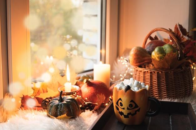 Halloween mit kürbissen, kaffee mit marshmallow auf der fensterbank