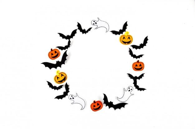 Halloween-modellkonzept. fliegende schwarze papierfledermäuse, kürbisse und geister auf weiß. runder rahmen