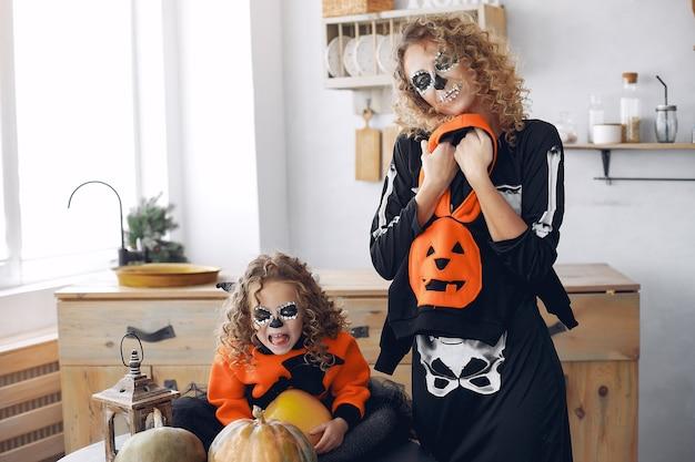 Halloween. mutter und tochter im halloween-kostüm im mexikanischen stil. familie zu hause mit kürbissen.