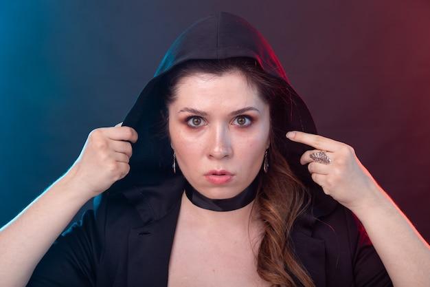 Halloween, mysteriöses und mystisches konzept - sexy brünette frau in der schwarzen kapuze.