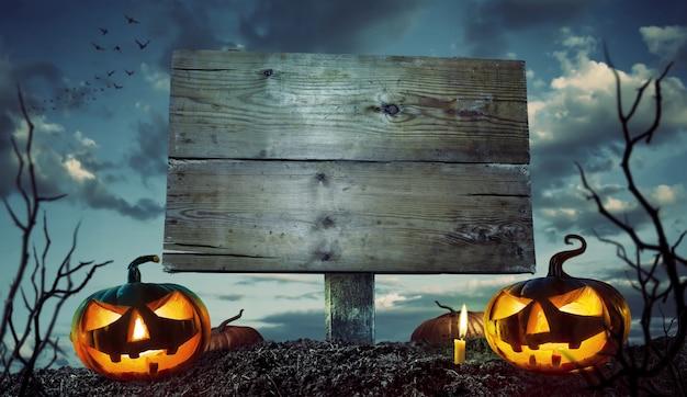 Halloween-nacht-konzept. leeres holzschild mit copyspace und furchtsamen kürbisen