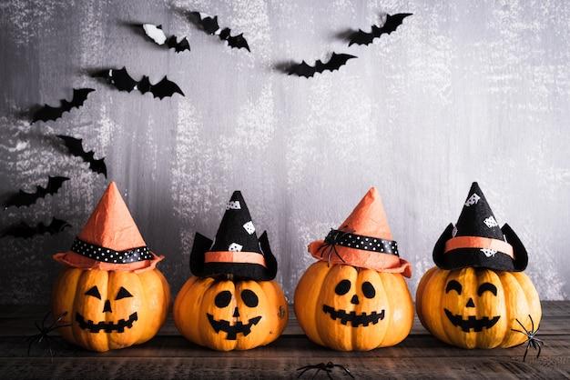 Halloween, orange geistkürbise mit hexenhut auf grauem hölzernem brett