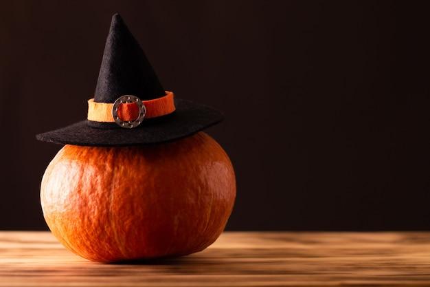 Halloween orange kürbis in einem hexenhut auf braunem hintergrund. platz kopieren.