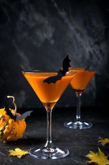 Halloween-orangensaftgetränk mit fledermäusen auf dunklem hintergrund, gruselig