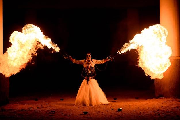 Halloween-paare, die mit flammenwerfer in den händen stehen. großes feuer
