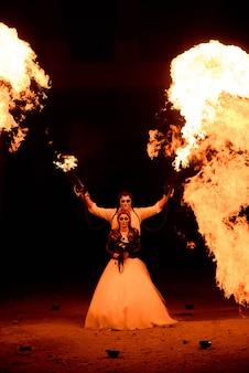 Halloween-paare, die mit flammenwerfer stehen. großes feuer