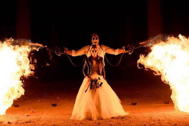 Halloween-paare, die mit flammenwerfer stehen.