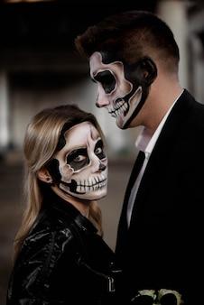 Halloween-paare, gekleidet im romantischen zombie der hochzeitskleidung