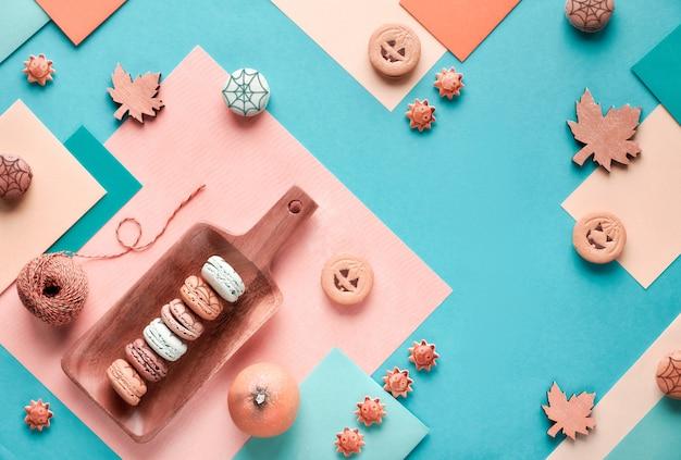 Halloween-papier in pastellfarben mit verzierten süßigkeiten und ahornblättern