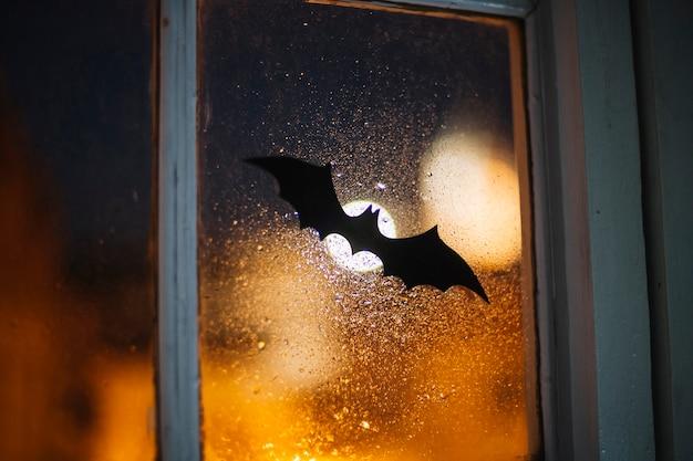 Halloween-papierfledermaus, die das fenster bedeckt mit regentropfen verziert