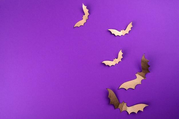 Halloween papierkunst. fliegende schwarze papierfledermäuse auf lila
