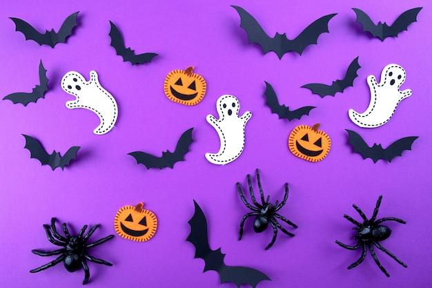 Halloween papierkunst. fliegende schwarze papierfledermäuse, kürbisse und geister auf lila.