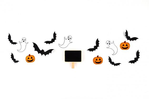Halloween papierkunst. fliegende schwarze papierfledermäuse, kürbisse und geister, schwarzes etikett auf weiß.