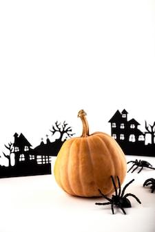 Halloween papierkunst. verlassenes dorf und kürbis auf weiß.