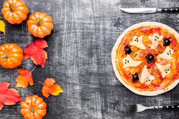 Halloween-pizza mit kürbis und blättern
