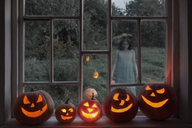 Halloween pumpins auf fensterbank mit geist außerhalb fenster