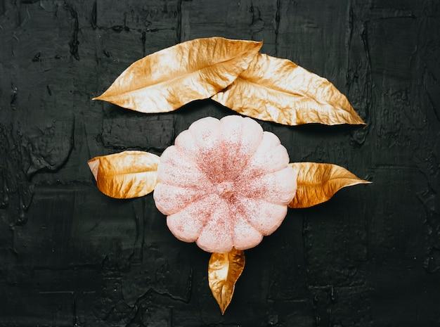 Halloween-rosa-funkelnkürbis und -gold verlässt auf schwarzem hintergrund