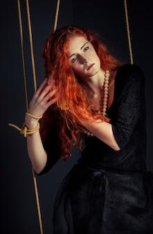 Halloween-rothaarigefrauen-marionettenpuppe gebunden mit seilen
