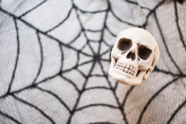 Halloween-schädel auf einem unscharfen hintergrund mit spinnennetzbeschaffenheit