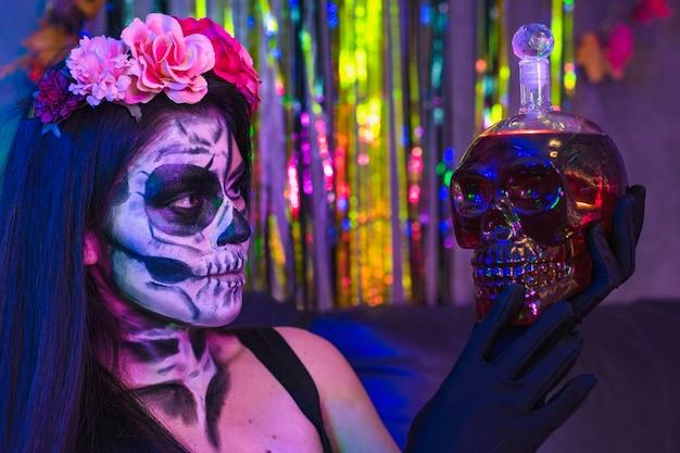 Halloween schädel catrina make-up, charmantes porträt der jungen frau im kostüm, das eine kristallschädelflasche in einer partei hält