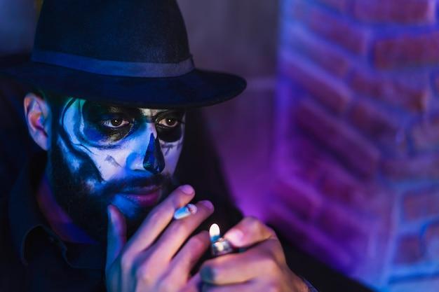 Halloween schädel catrina make-up, charmantes porträt des jungen mannes im kostüm, das eine zigarette hält