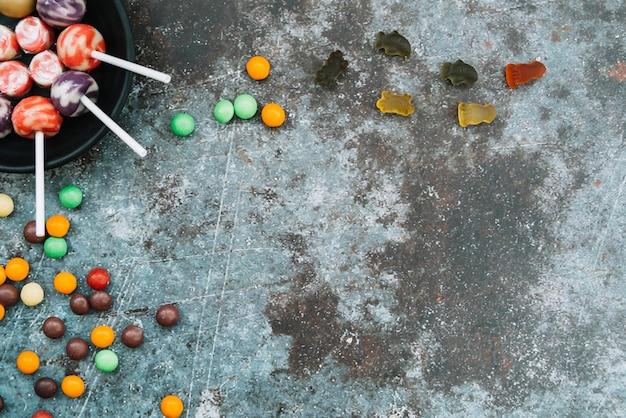Halloween süßes sonst gibt's saures süßigkeiten, die auf grauer oberfläche liegen