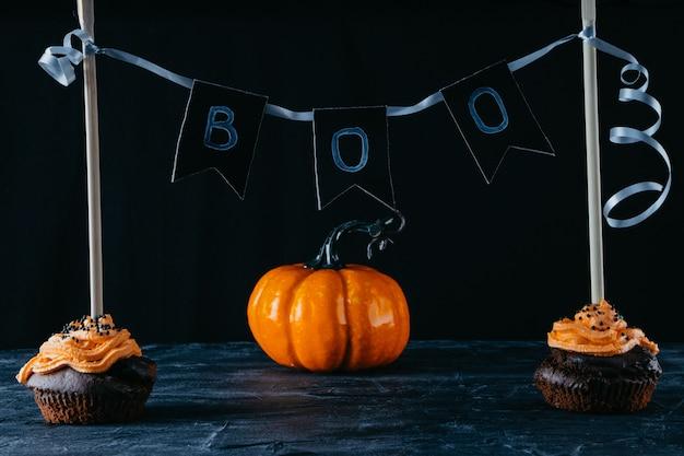 Halloween-süßigkeiten, schokoladencupcakes und kürbis