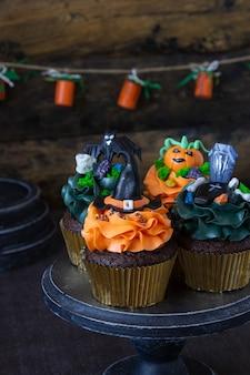 Halloween-symbole, vorbereitung für den urlaub. orange kürbis cupcakes und holzdekor.