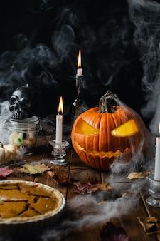 Halloween-tabelle mit kürbislaterne, spinnennetz, kerzen und rauche