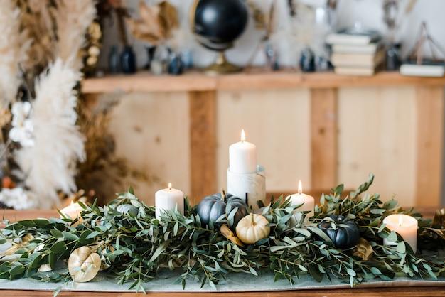 Halloween-tabelleneinstellung auf dunklem hintergrund. gericht mit süßigkeiten auf einem dunklen tisch mit schwarz-goldenem kürbis. trendiges urlaubskonzept mit flacher lage und draufsicht.