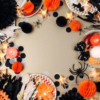 Halloween-tabelleneinstellung. rahmen aus schwarz-orangefarbenem partydeko. flache lage, ansicht von oben