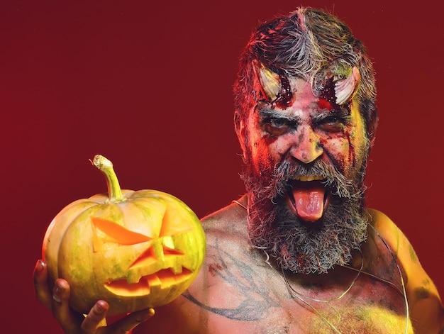 Halloween-teufel mit blutigen hörnern zeigt zunge auf rotem hintergrund