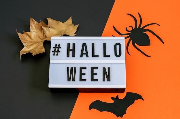 Halloween-text auf schwarz-orange papier mit goldenen blättern und schwarzer dekorativer fledermaus und spinne. flach liegen