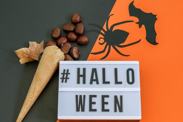 Halloween-text auf schwarz-orangeem papier mit waffeleistüte mit kastanien und dekorativer fledermaus und spinne. flach liegen