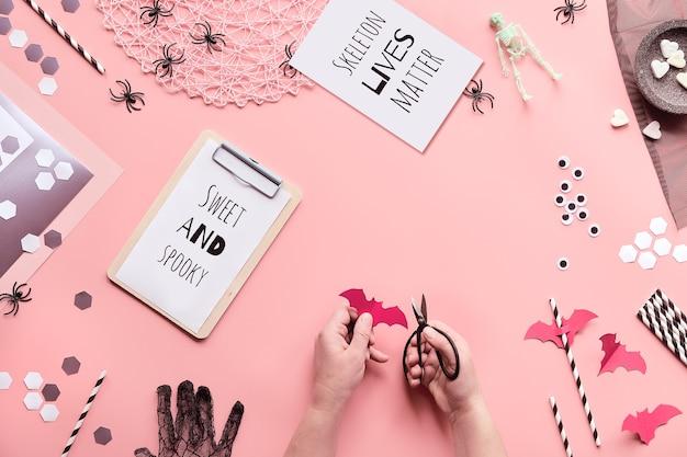 Halloween-textkarten mit text sweet and spooky und skeleton lives matter. hände mit der schere schneiden papierdekorationen auf rosa.
