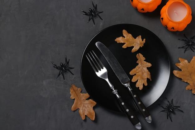 Halloween-tischdekoration ist mit kürbisförmigen kerzen, spinnen und horror-party-dekor auf schwarzem tisch dekoriert. platz für text.