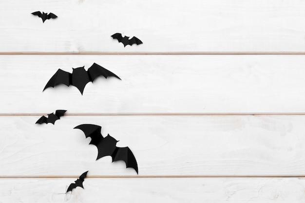 Halloween und dekorationskonzept - papierschläger, die auf hölzernes copyspace fliegen