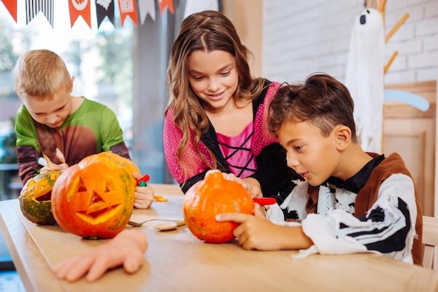 Halloween und familie. drei aufgeregte niedliche kinder, die kürbisse verzieren, während sie sich für halloween-familienfeier vorbereiten
