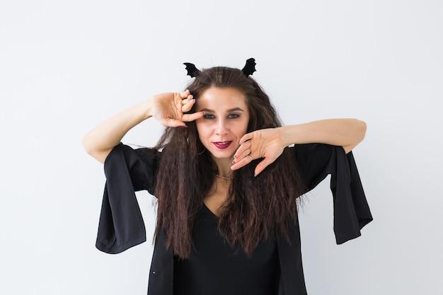 Halloween und feiertagskonzept - hexenfrau mit jack o'lantern kürbis